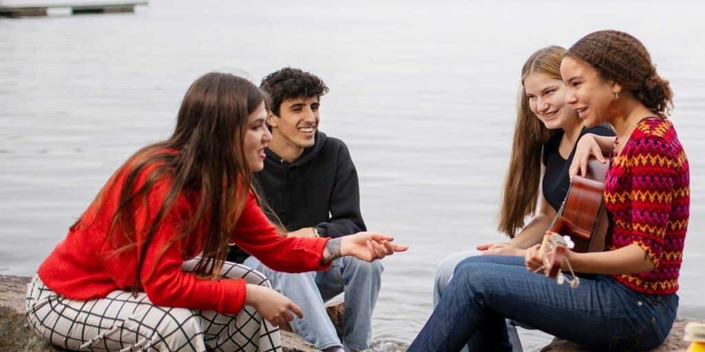 aikuinen ja nuoret juttelevat rannalla