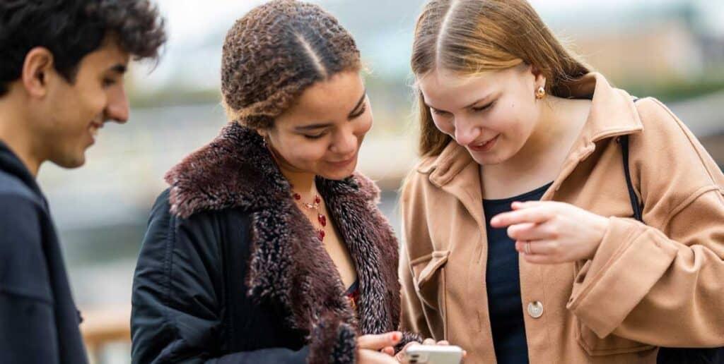 nuoret katselevat jotain puhelimen näytöltä