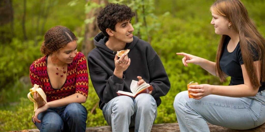 nuoret syövät eväitä metsässä