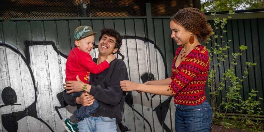 nuoret leikkivät iloisesti lapsen kanssa