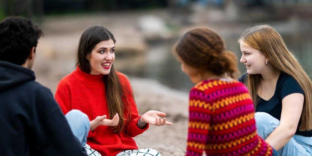 Aikuinen kertoo tarinaa rantakalliolla, nuoret kuuntelevat kiinnostuneena