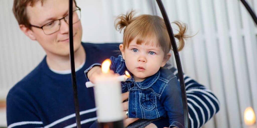 lapsi ja vanhempi katsovat kynttilää