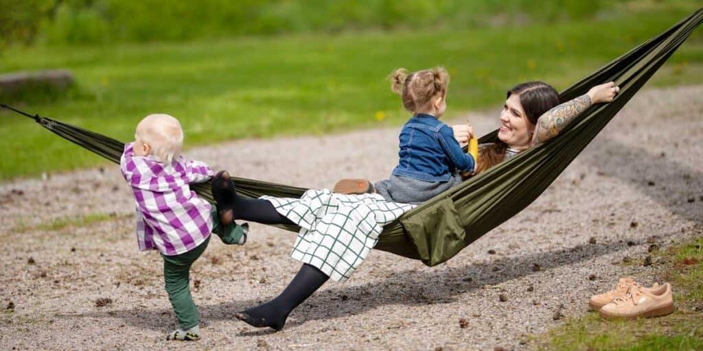 Aikuinen lepää riippumatossa ja lapset leikkii ympärillä