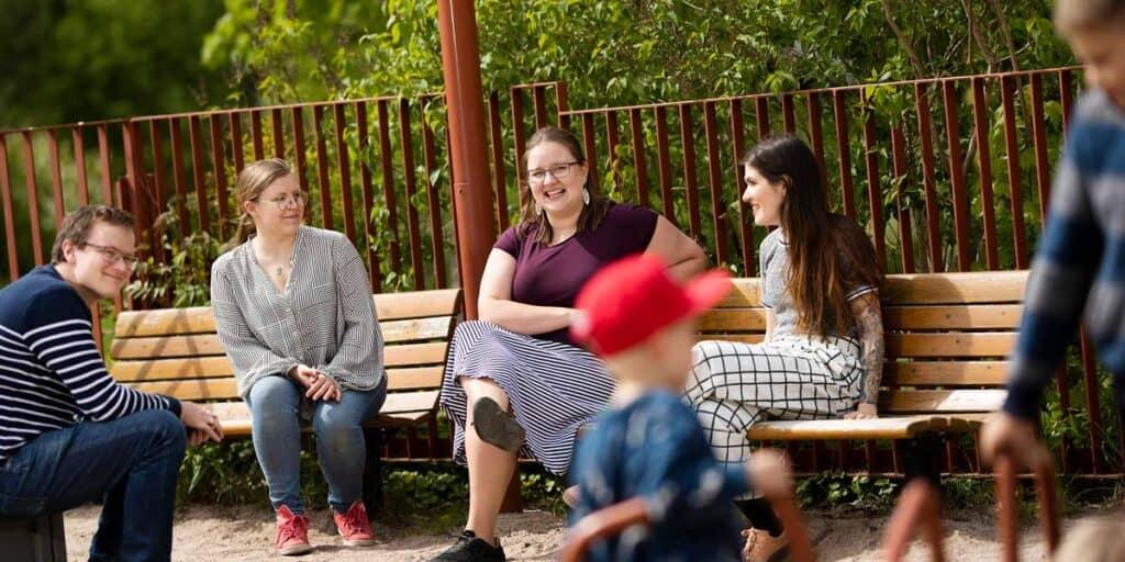 Aikuiset katsovat lapsia leikkimässä