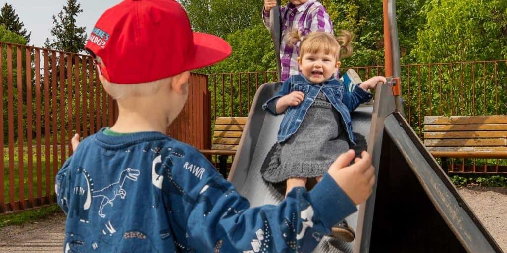 lapsi laskee liukumäkeä toista lasta kohti