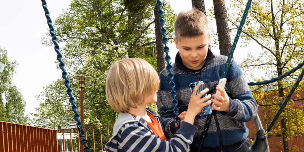 kouluikäiset juttelevat ja katsovat jotain puhelimen näytöltä