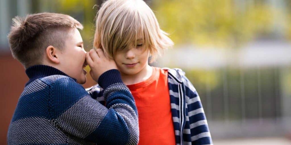 kouluikäinen kuiskaa toisen lapsen korvaan