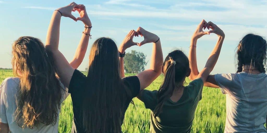 Joukko tyttöjä rivissä selin kameraan pellolla