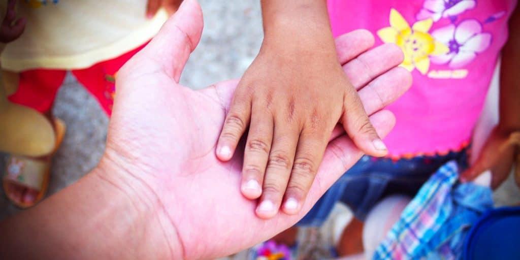 Lapsi laskee kätensä aikuisen kädelle