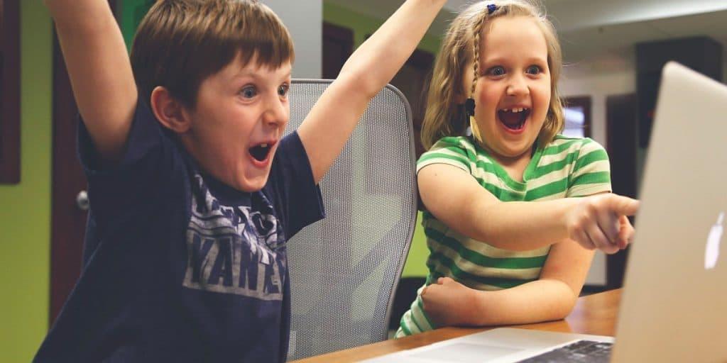 Kaksi lasta tietokoneella onnellisina