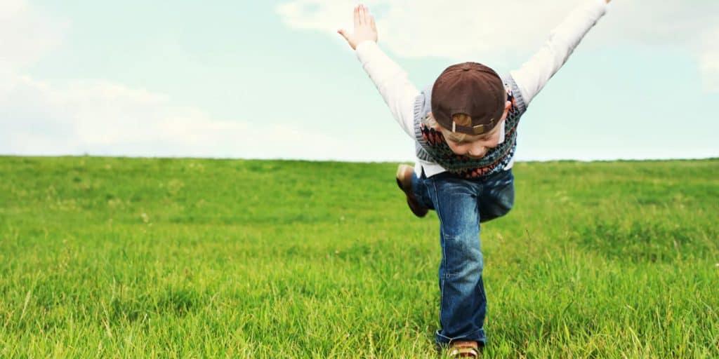 Lapsi leikkii niityllä
