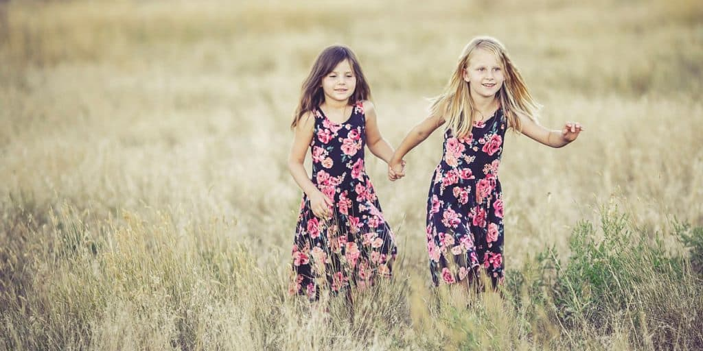 Kaksi nuorta tyttöä juoksemassa käsikkäin pellolla