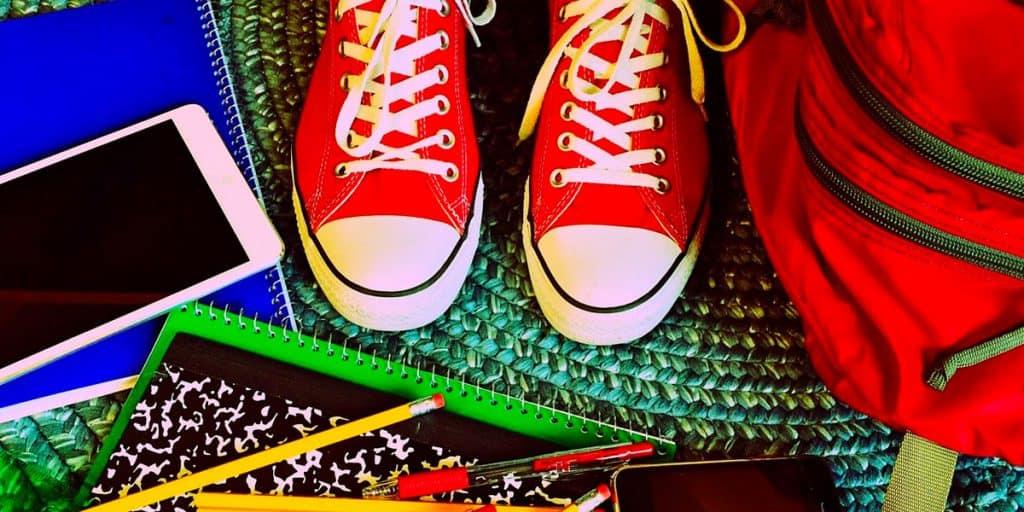 Koulutavaroita ja jalat joissa punaiset tennarit