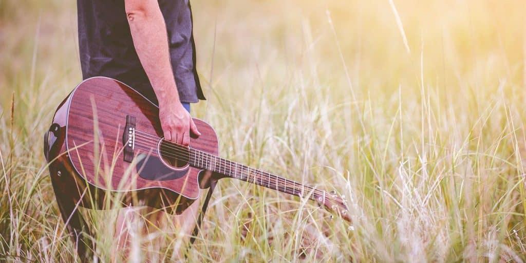 Mies pellolla kitaran kanssa