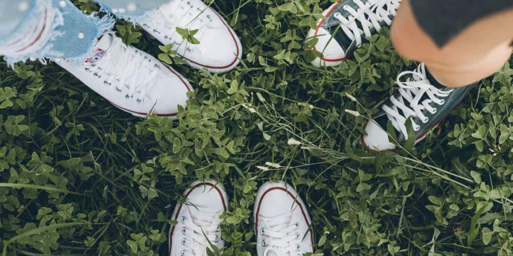 Kolmet tennarit kärjet vastakkain nurmikolla.