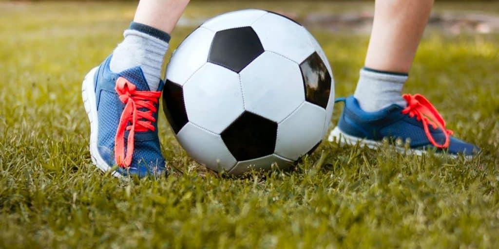 Jalkapallo ja lapsen jalat.