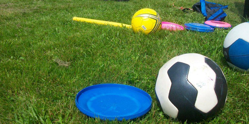 Palloja ja frisbie-kiekkoja nurmikolla.