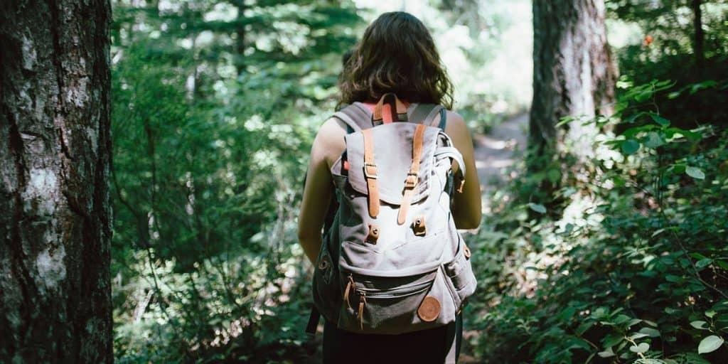 Naisella on reppu selässä. Taustalla näkyy metsä.