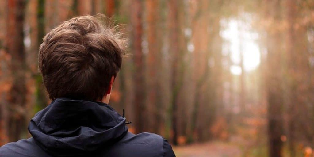 Nuoren selkä ja niska etuallla, taustalla metsämaisema.
