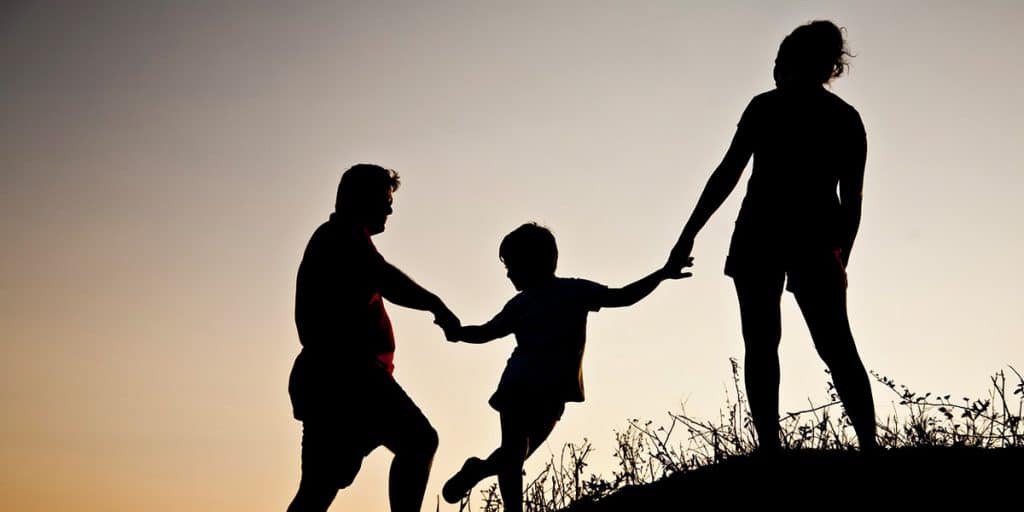 Perhe kiipeämässä kukkulalle