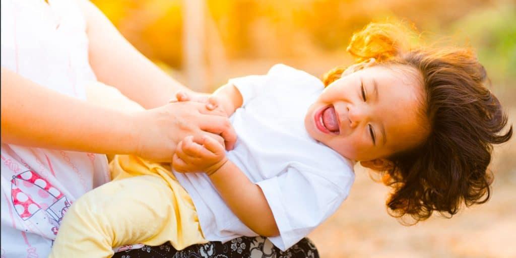 Lapsi leikkii sylissä