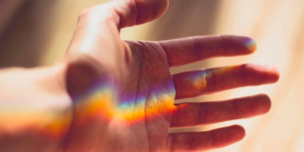 Valo heijastaa avoimelle kädelle sateenkaaren