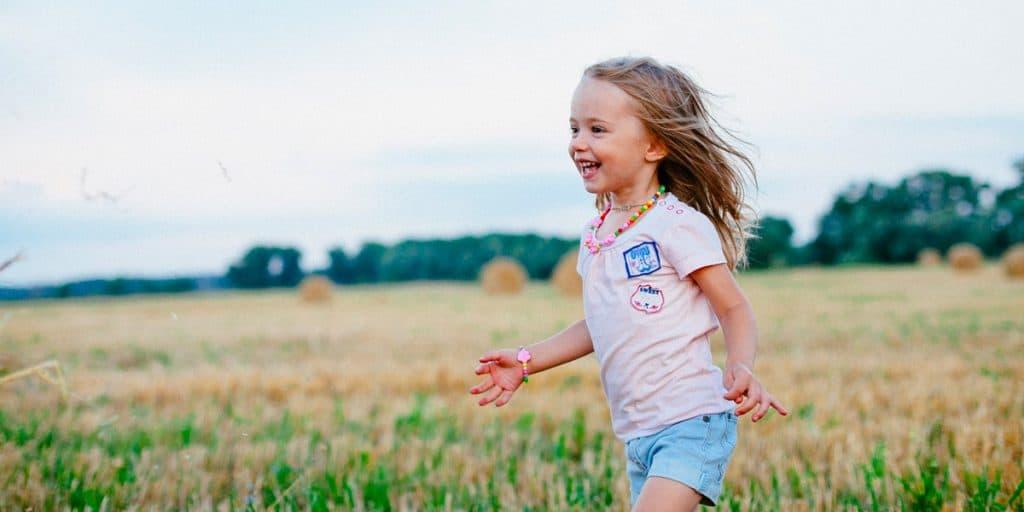 Lapsi juoksee pellolla.