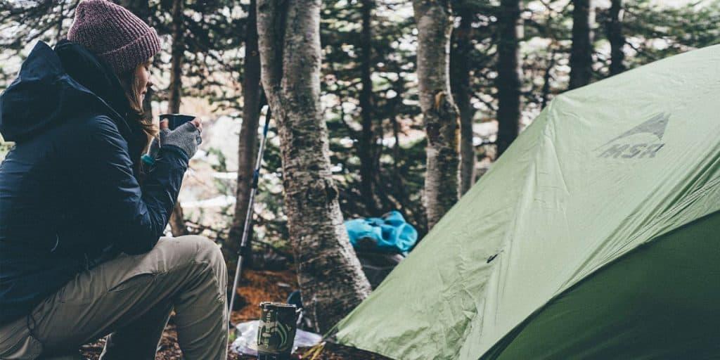 Tyttö juo kahvia teltan edustalla