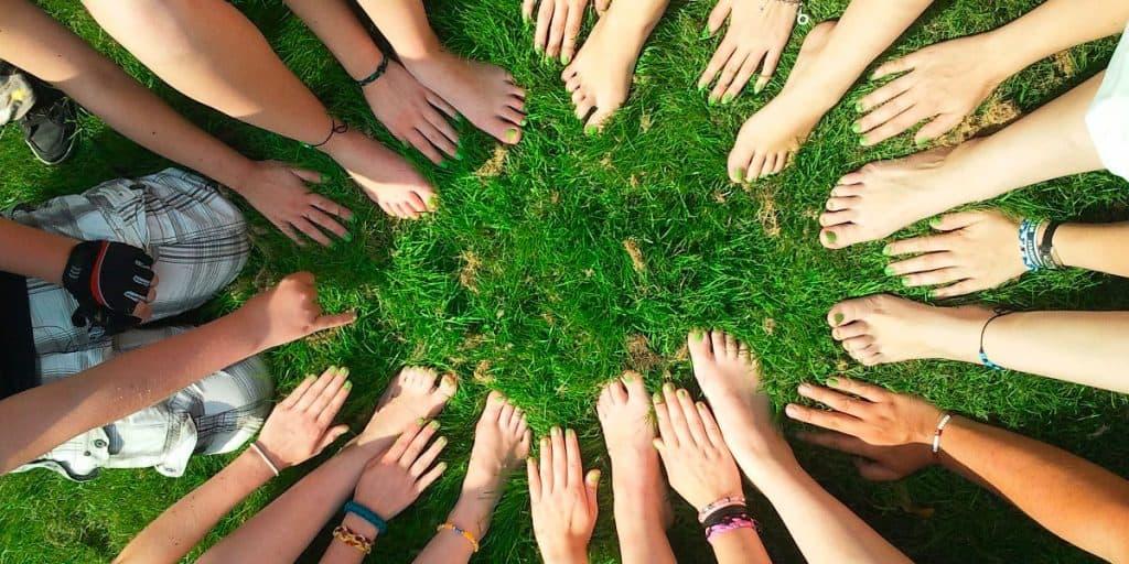 Joukko ojennettuja käsiä ja jalkoja muodostaa ympyrän