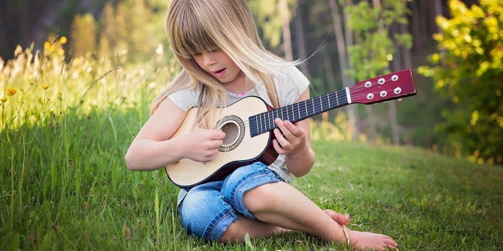 Lapsi soittamassa ukulelea
